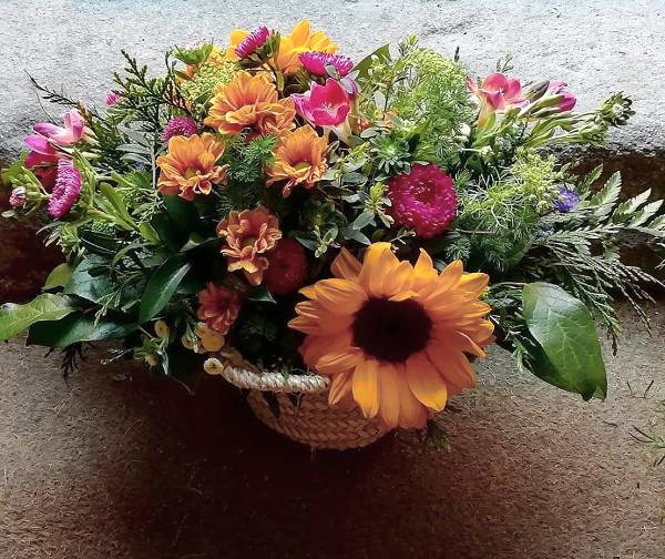 centro de mimbre con flores silvestres y girasol